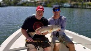 two men in a boat with a red fish