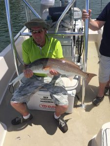 gentleman holding a red fish in boat off Sarasota