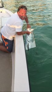 man in boat lifting a large tarpon out of the water